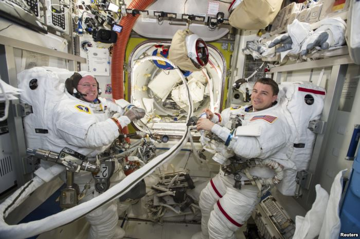 FILE - NASA astronauts Reid Wiseman, right, and Barry Wilmore work inside the