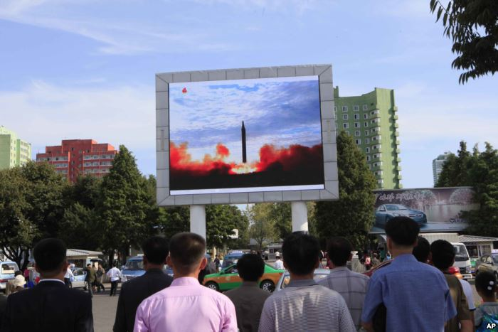 FILE - People watch a launching of a Hwasong-12 strategic ballistic rocket ai