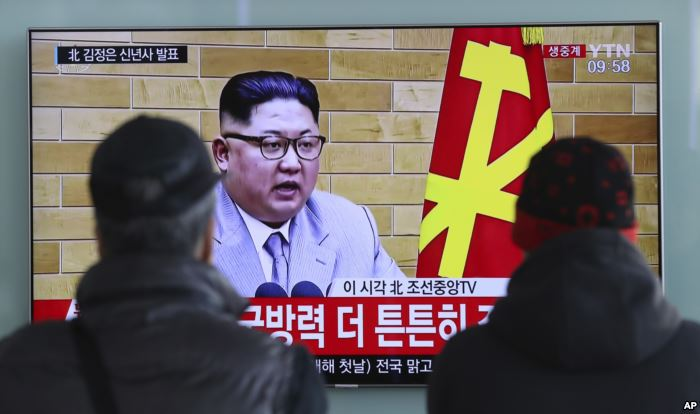 FILE - South Koreans watch a TV news program showing North Korean leader Kim