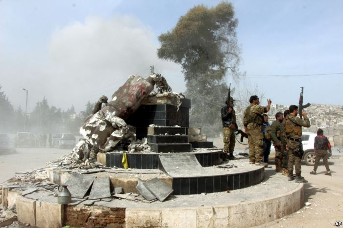FILE - Turkey-backed Free Syrian Army soldiers celebrate around a statue of K