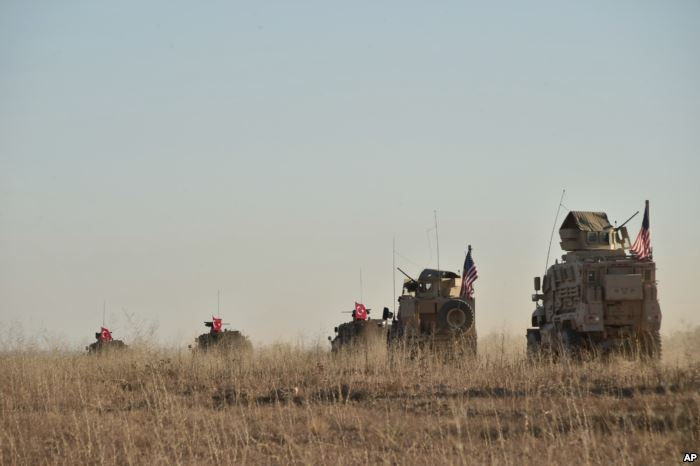 FILE - Turkish and U.S. troops conduct joint patrols around the Syrian town o