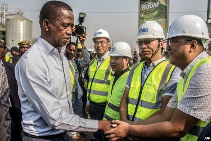 FILE - Zambian President Edgar Lungu, left, greets Chinese workers during a w