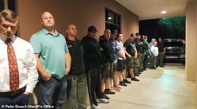 Law enforcement wait outside the veterinary hospital to pay tribute to the fallen K9 Cigo