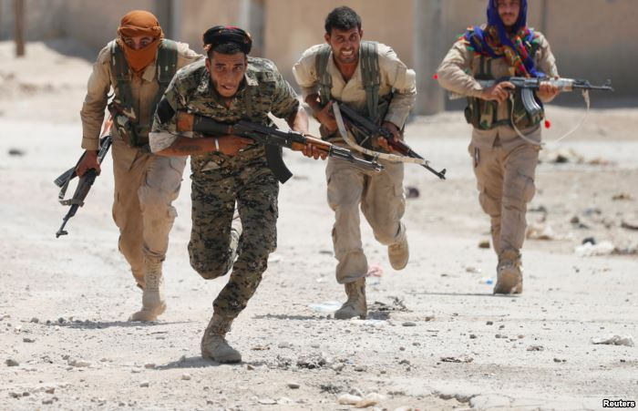 Kurdish fighters from the People's Protection Units (YPG) run across a st