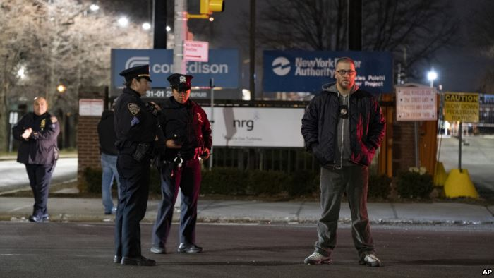 Law enforcement personnel stand in front of a Con Edison facility in the Quee