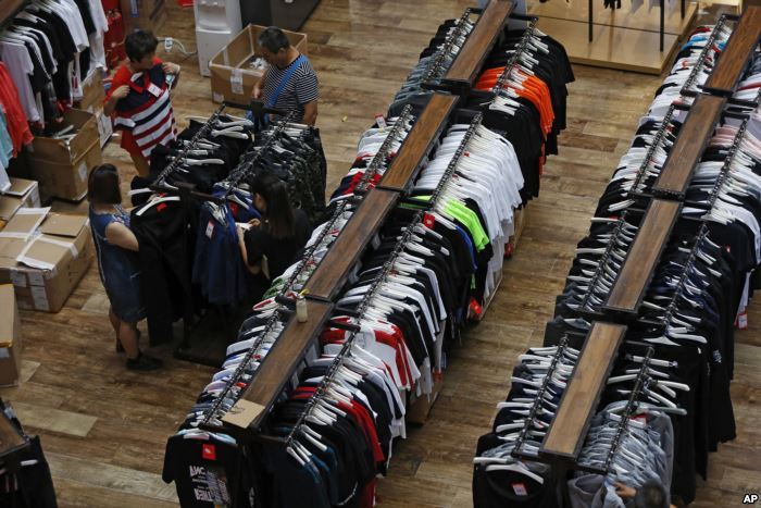 People try garments at a retail and wholesale clothing mall in Beijing, July