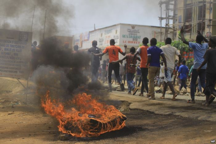 Protesters walk past a burning tire in the eastern Congolese town of Beni, De