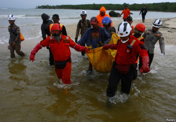 Rescue workers carry a body bag containing the remains of a victim of a tsuna