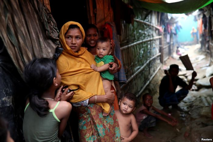 Rohingya refugees are seen outside their makeshift tent in the Kutupalong cam