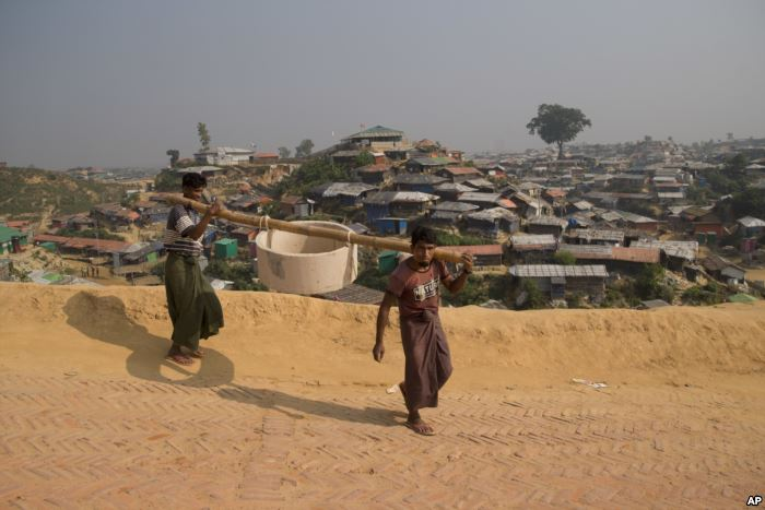 Rohingya refugees carry a hume pipe in Balukhali refugee camp near Cox's