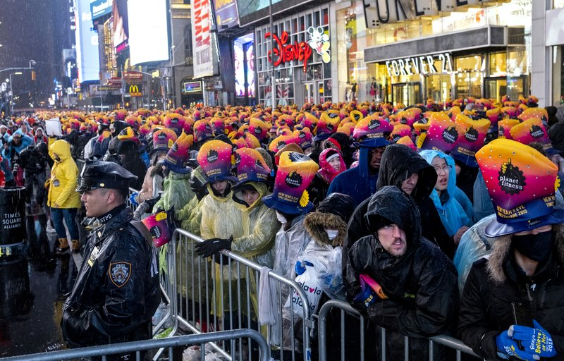 A New York City police officer stands near revelers gathered at Times Square in New York, Monday, Dec. (AP Photo/Craig Ruttle)