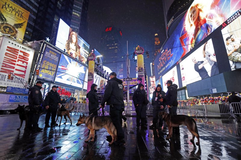 New York City K-9 officers stand near revelers gathered in Times Square in New York, Monday, Dec. 31, 2018, as they take part in a New Year's Eve celebration. (AP Photo/Adam Hunger)
