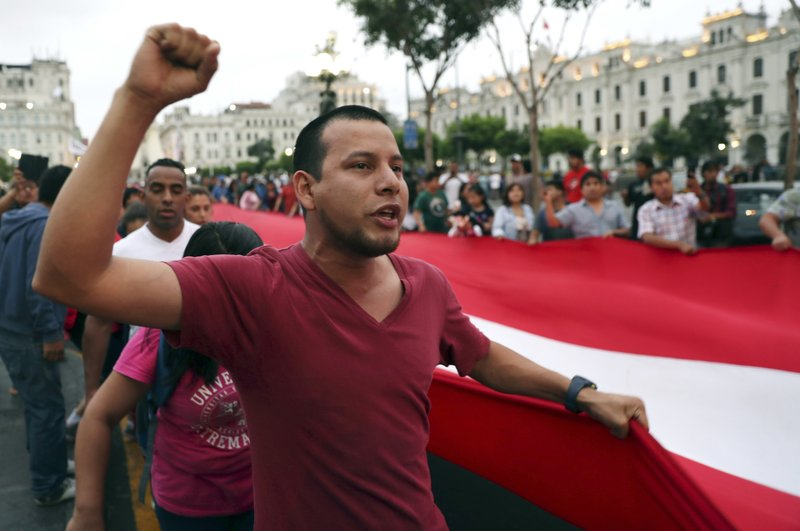 Demonstrators protest at San Martin Plaza in Lima, Peru, Tuesday, Jan. 1, 2019, over Attorney General Pedro Chavarry's dismissal of a team investigating the sweeping Odebrecht corruption case. (AP Photo/Martin Mejia)