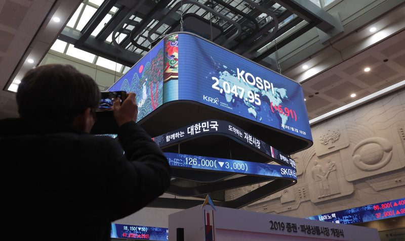 A man takes a photo of screens showing the Korea Composite Stock Price Index (KOSPI) at the Korea Exchange in Seoul, South Korea, Wednesday, Jan. (AP Photo/Lee Jin-man)