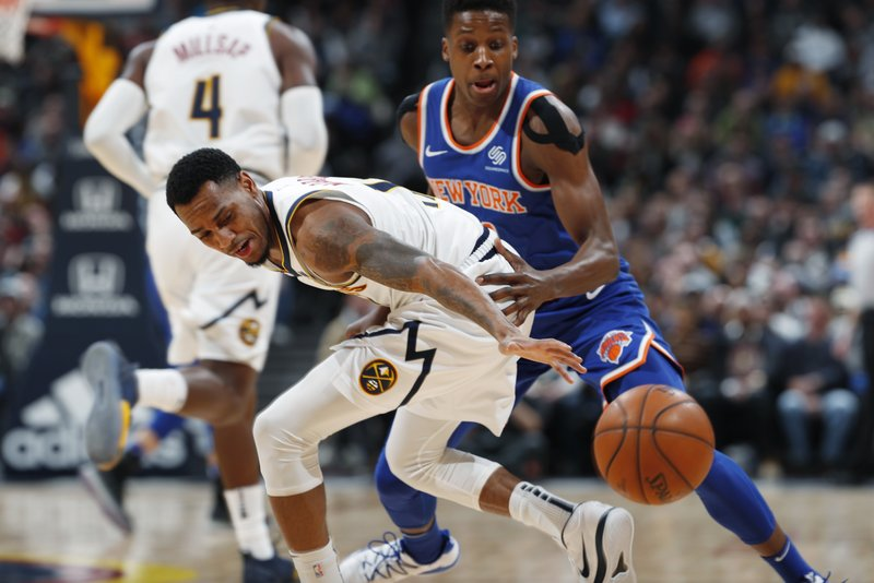 Denver Nuggets guard Monte Morris, front, struggles to pick up a loose ball as New York Knicks guard Frank Ntilikina defends during the first half of an NBA basketball game Tuesday, Jan. (AP Photo/David Zalubowski)