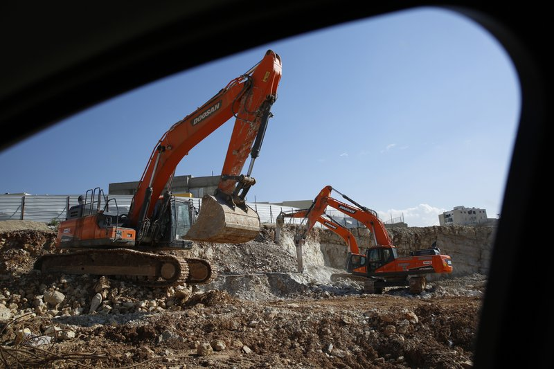 In this Tuesday, Jan. 1, 2019 photo, men work on a new housing project in the West Bank settlement of Modin ilit. (AP Photo/Ariel Schalit)