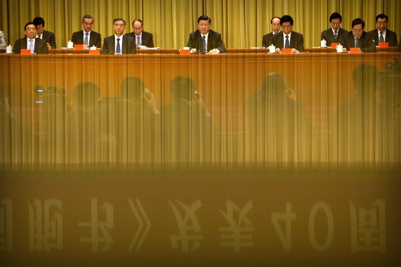A banner is reflected in a polished surface as Chinese President Xi Jinping, center, speaks during an event to commemorate the 40th anniversary of the Message to Compatriots in Taiwan at the Great Hall of the People in Beijing, Wednesday, Jan. (AP Photo/Mark Schiefelbein, Pool)