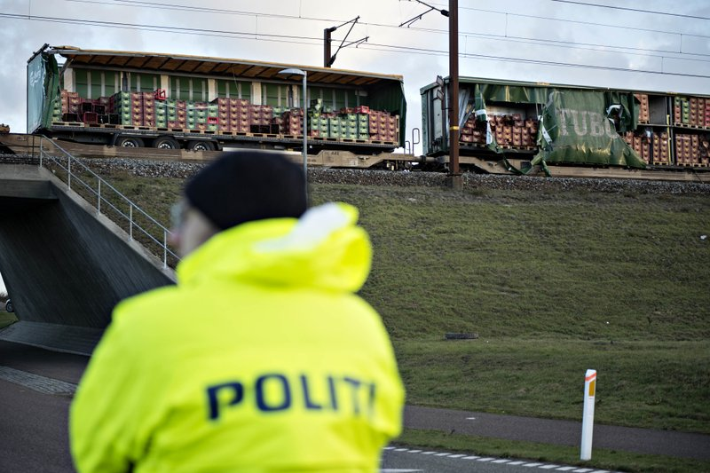 A police officer looks on near a damaged cargo train compartment near the Storebaelt bridge, near Nyborg in Denmark, Wednesday, Jan. (Michael Bager/Ritzau Scanpix via AP)