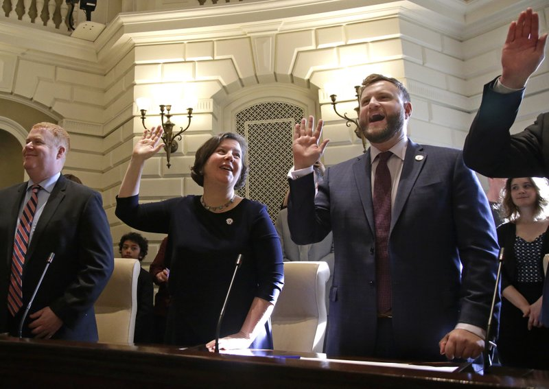 Newly-elected Mass. State Senator Jo Comerford, middle, takes the oath of office in the Senate Chamber at the Massachusetts Statehouse, Wednesday, Jan. (AP Photo/Elise Amendola)