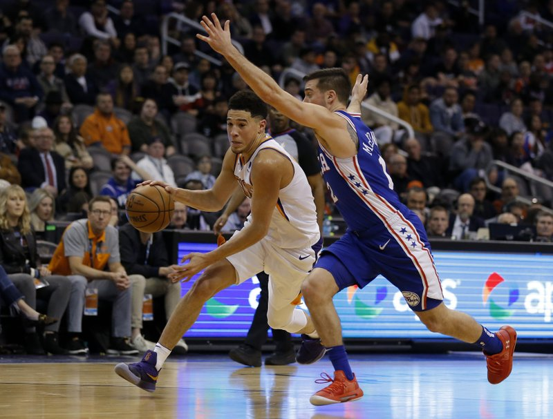 Phoenix Suns guard Devin Booker (1) drives past Philadelphia 76ers guard T.J. McConnell in the first half during an NBA basketball game, Wednesday, Jan. (AP Photo/Rick Scuteri)