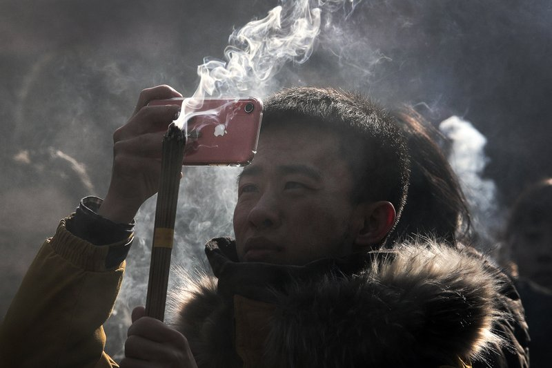 In this Tuesday, Jan. 1, 2019, photo, a Chinese man uses iPhone to take picture as he prays for health and fortune on the first day of the New Year at Yonghegong Lama Temple in Beijing. (AP Photo/Andy Wong)