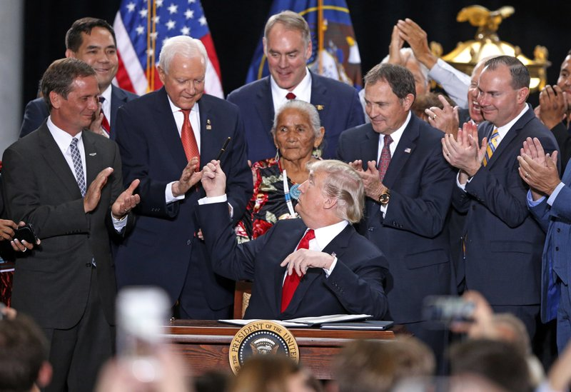 File - In this Dec. 4, 2017, file photo, President Donald Trump, center, hands a pen to Sen. Orrin Hatch, R-Utah, after signing a proclamation to shrink the size of Bears Ears and Grand Staircase Escalante national monuments at the Utah State Capitol in Salt Lake City. (AP Photo/Rick Bowmer, File)