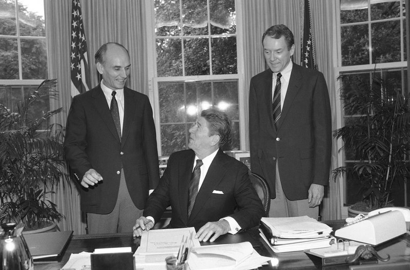 FILE - In this Sept. 28, 1984, file photo, U.S. President Ronald Reagan signs S. 2155, the Utah Wilderness Act of 1984 in the White House Oval Office in Washington as Utah Senator Orrin Hatch looks on. (AP Photo/Barry Thumma, File)