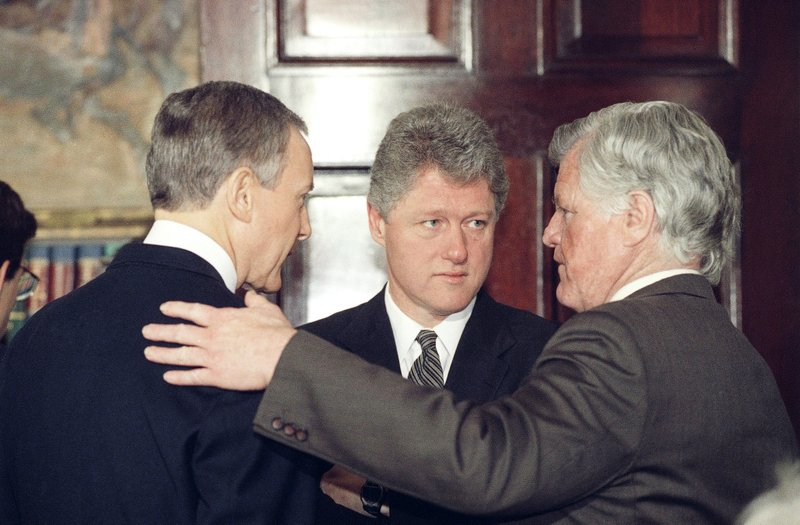 FILE - In this March 12, 1993, file photo, President Bill Clinton huddles with Sen. Orrin Hatch, R-Utah, left, and Sen. (AP Photo/Barry Thumma, File)