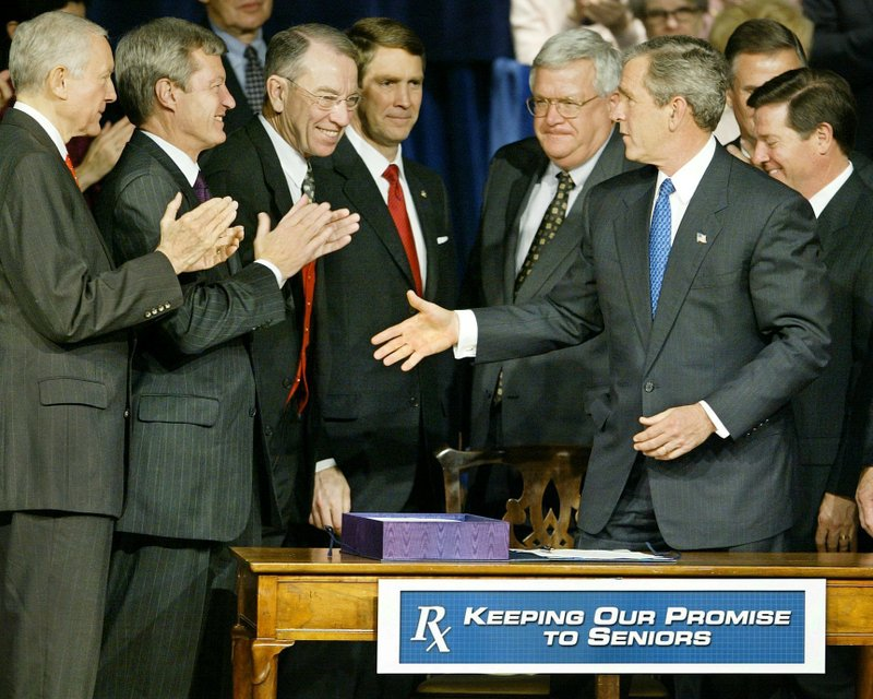 FILE - In this Dec. 8, 2003, file photo President George W. Bush greets applauding Congressional leaders as he signs into law the Medicare prescription drug benefit at the Daughters of the American Revolution's Constitution Hall in Washington. (AP Photo/J. Scott Applewhite, File)