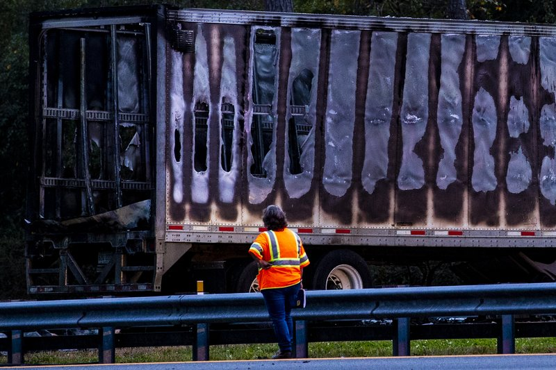 Workers look at a charred semi-truck after a wreck with multiple fatalities on Interstate 75, south of Alachua, near Gainesville, Fa. (Lauren Bacho/Star-Banner via AP)