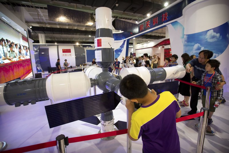 FILE - In this June 10, 2017 file photo, visitors look at a model of China's Tiangong-1 space station at the China Beijing International High-Tech Expo in Beijing. (