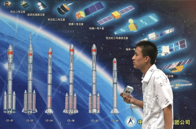 FILE - In this file photo taken Thursday, Oct. 6, 2005, a Chinese man walks past an illustration showing various Long March space rockets and satellites on exhibit at a local Beijing park in China. (AP Photo)