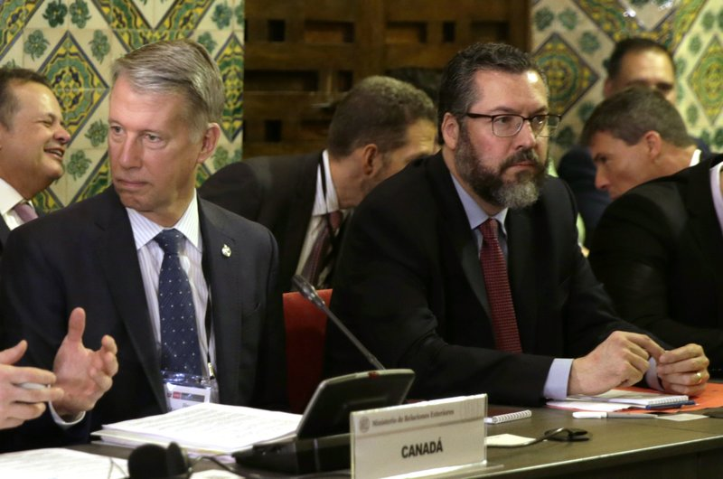 Brazil's Foreign Minister Ernesto Araujo, right, and Canada's Parliamentary Secretary to the Minister of Foreign Affairs Andrew Leslie, left, attend a meeting of the Lima Group concerning Venezuela in Lima, Peru, Friday, Jan. (AP Photo/Martin Mejia)