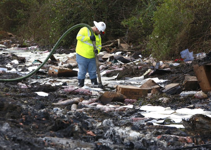A worker with the environmental clean up company AAG Environmental works to remove fuel spilled at the scene of Thursday's multi-vehicle accident that caused multiple fatalities on Interstate 75 between Alachua and Gainesville, Fla. (Brad McClenny/The Gainesville Sun via AP)