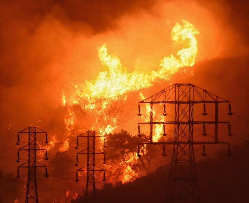 FILE - In this Dec. 16, 2017, file photo provided by the Santa Barbara County Fire Department, flames burn near power lines in Sycamore Canyon near West Mountain Drive in Montecito, Calif. (Mike Eliason/Santa Barbara County Fire Department via AP, File)