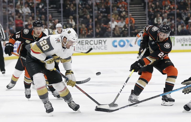 Vegas Golden Knights' William Carrier, left, is defended by Anaheim Ducks' Brian Gibbons, right, during the first period of an NHL hockey game Friday, Jan. (AP Photo/Marcio Jose Sanchez)