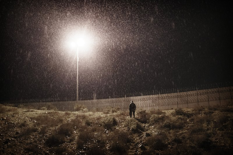 A U.S. Border Protection officer stands under the rain as he watches the border fence between San Diego, Calif. (AP Photo/Daniel Ochoa de Olza)