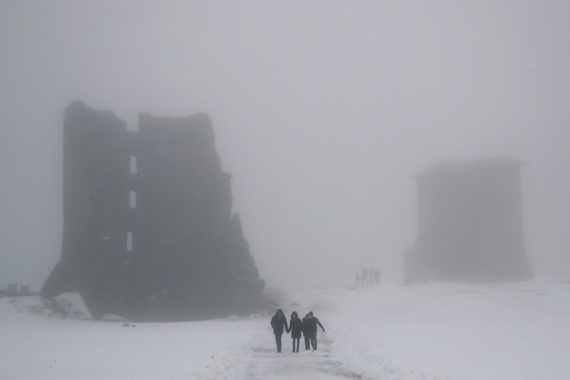 People walk past the ruins of a medieval castle on a foggy day in the Belarusian town of Novogrudok, 150 kilometers (93 miles) west of the capital Minsk, Sunday, Dec. (35 Fahrenheit). (AP Photo/Sergei Grits)