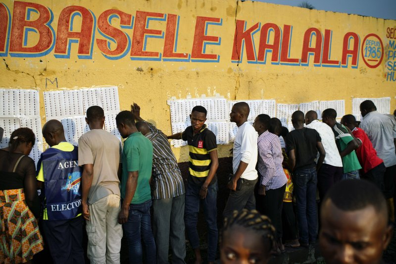 Election officials tape voter registration lists to a wall of the Les Anges primary school in Kinshasa, Congo, as voters start to check their names, Sunday Dec. (AP Photo/Jerome Delay)