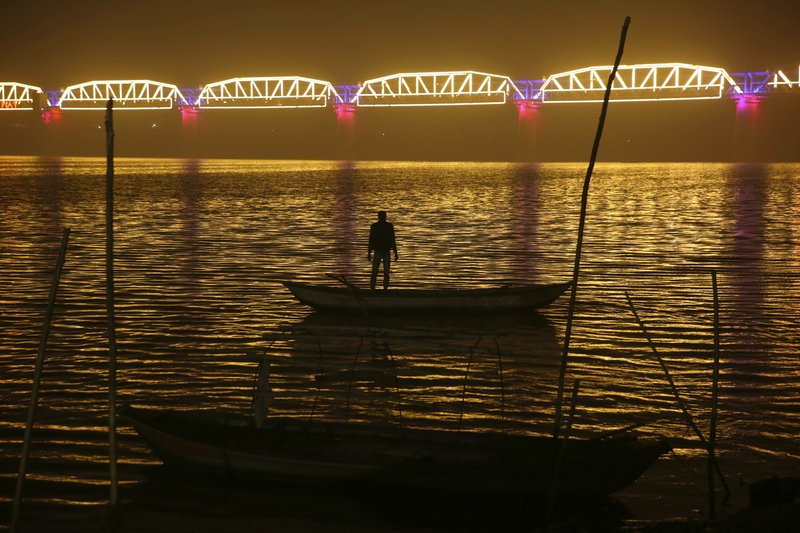 A person stands in a boat as he looks at an illuminated railway bridge across the river Yamuna ahead of the upcoming Kumbh Mela festival in Allahabad, India, Monday, Dec. (AP Photo/Rajesh Kumar Singh)