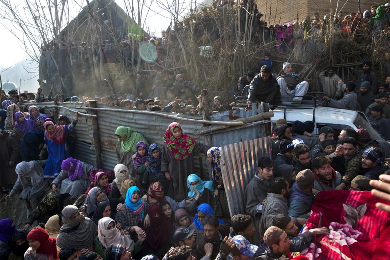 Villagers watch as a vehicle carrying the body of local rebel Muzamil Ahmed Dar arrives at his residence in Rahmoo village south of Srinagar, Indian-controlled Kashmir, Saturday, Dec. (AP Photo/ Dar Yasin)