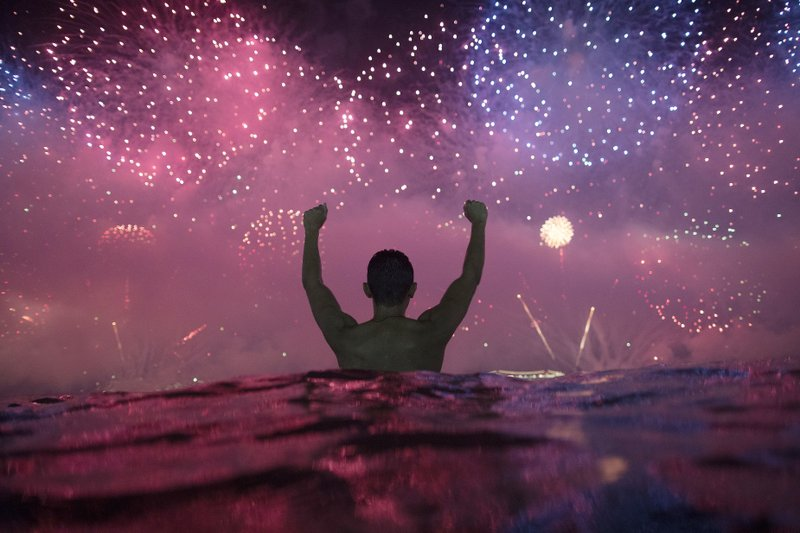 A man stands in the water as he watches fireworks over Copacabana Beach during New Year's celebrations in Rio de Janeiro, Brazil, Tuesday, Jan. (AP Photo/Leo Correa)