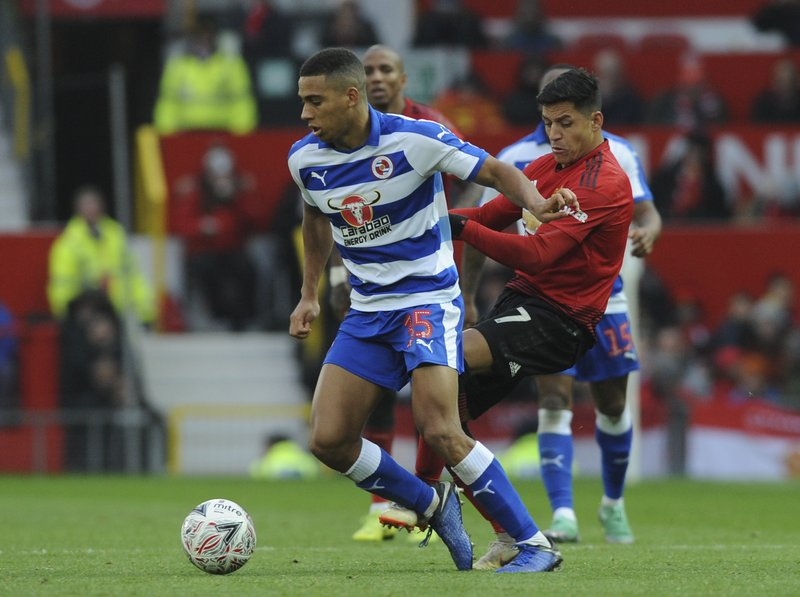 Reading's Callum Harriott, left, and Manchester United's Alexis Sanchez challenge for the ball during the English FA Cup third round soccer match between Manchester United and Reading at Old Trafford in Manchester, England, Saturday, Jan. (AP Photo/Rui Vieira)