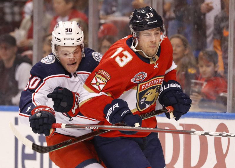 Columbus Blue Jackets left wing Eric Robinson (50) and Florida Panthers defenseman Mark Pysyk (13) battle for the puck during the first period of an NHL hockey game, Saturday, Jan. (AP Photo/Wilfredo Lee)