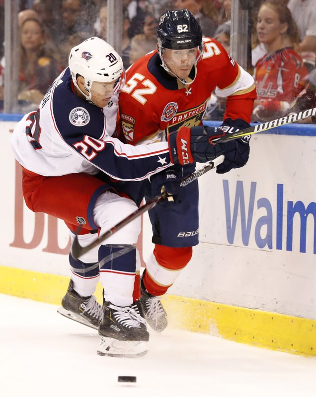 Columbus Blue Jackets center Riley Nash (20) slams Florida Panthers defenseman MacKenzie Weegar (52) into the boards during the first period of an NHL hockey game, Saturday, Jan. (AP Photo/Wilfredo Lee)