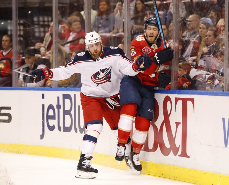 Columbus Blue Jackets center Brandon Dubinsky (17) slams Florida Panthers left wing Mike Hoffman (68) into the boards during the first period of an NHL hockey game, Saturday, Jan. (AP Photo/Wilfredo Lee)