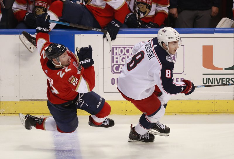 Florida Panthers right wing Troy Brouwer (22) and Columbus Blue Jackets defenseman Zach Werenski (8) battle for the puck during the second period of an NHL hockey game, Saturday, Jan. (AP Photo/Wilfredo Lee)