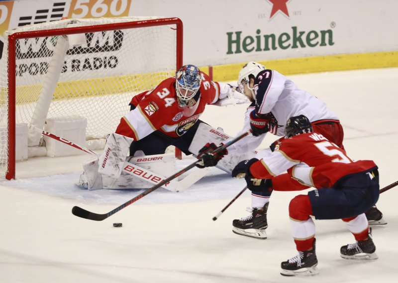 Columbus Blue Jackets right wing Josh Anderson, center, attempts a shot against Florida Panthers goaltender James Reimer (34) and defenseman MacKenzie Weegar (52) during the second period of an NHL hockey game, Saturday, Jan. (AP Photo/Wilfredo Lee)