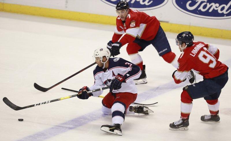 Columbus Blue Jackets defenseman Seth Jones (3) battles for the puck with Florida Panthers right wing Juho Lammikko (91) and center Colton Sceviour (7) during the second period of an NHL hockey game, Saturday, Jan. (AP Photo/Wilfredo Lee)
