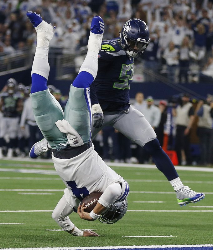 Dallas Cowboys quarterback Dak Prescott (4) flies for the goal line and makes a first down against Seattle Seahawks defensive end Frank Clark (55) during the second half of the NFC wild-card NFL football game in Arlington, Texas, Saturday, Jan. (AP Photo/Ron Jenkins)